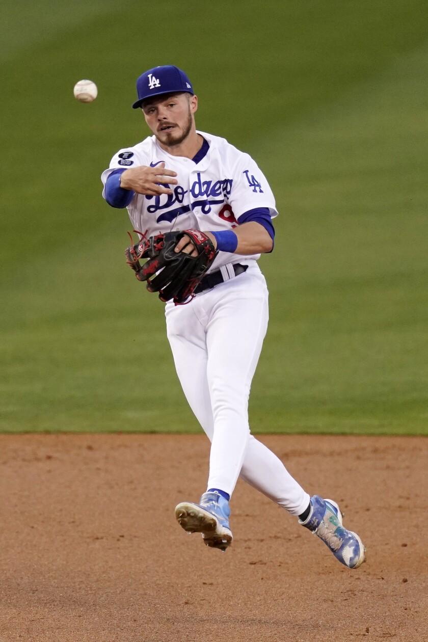 El segunda base de los Dodgers de Los Ángeles Gavin Lux elimina al jugador de los Marineros de Seattle Dylan Moore en primera base, en el segundo inning de su juego de interligas el martes 11 de mayo de 2021 en Los Ángeles. (AP Foto/Mark J. Terrill)