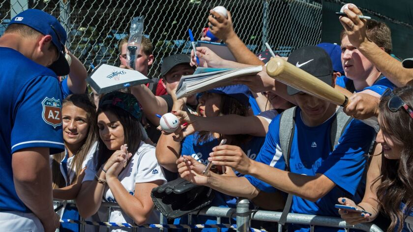 Fans jockey for position to get autographs from L.A. Dodger Corey Seager after a spring-training session in Arizona last year.