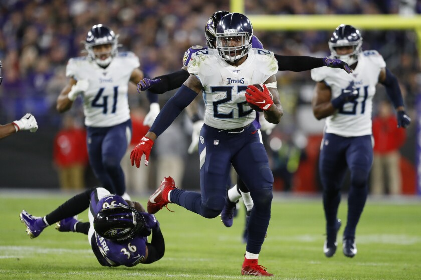 Tennessee Titans running back Derrick Henry (22) runs past Baltimore Ravens strong safety Chuck Clark (36) during the second half of NFL divisional playoff game Saturday in Baltimore.