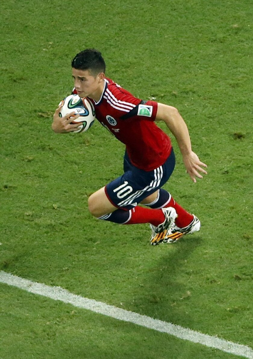 Colombia's James Rodriguez grabs the ball after scoring on a penalty during the World Cup quarterfinal soccer match between Brazil and Colombia at the Arena Castelao in Fortaleza, Brazil, Friday, July 4, 2014. (AP Photo/Fabrizio Bensch, pool)