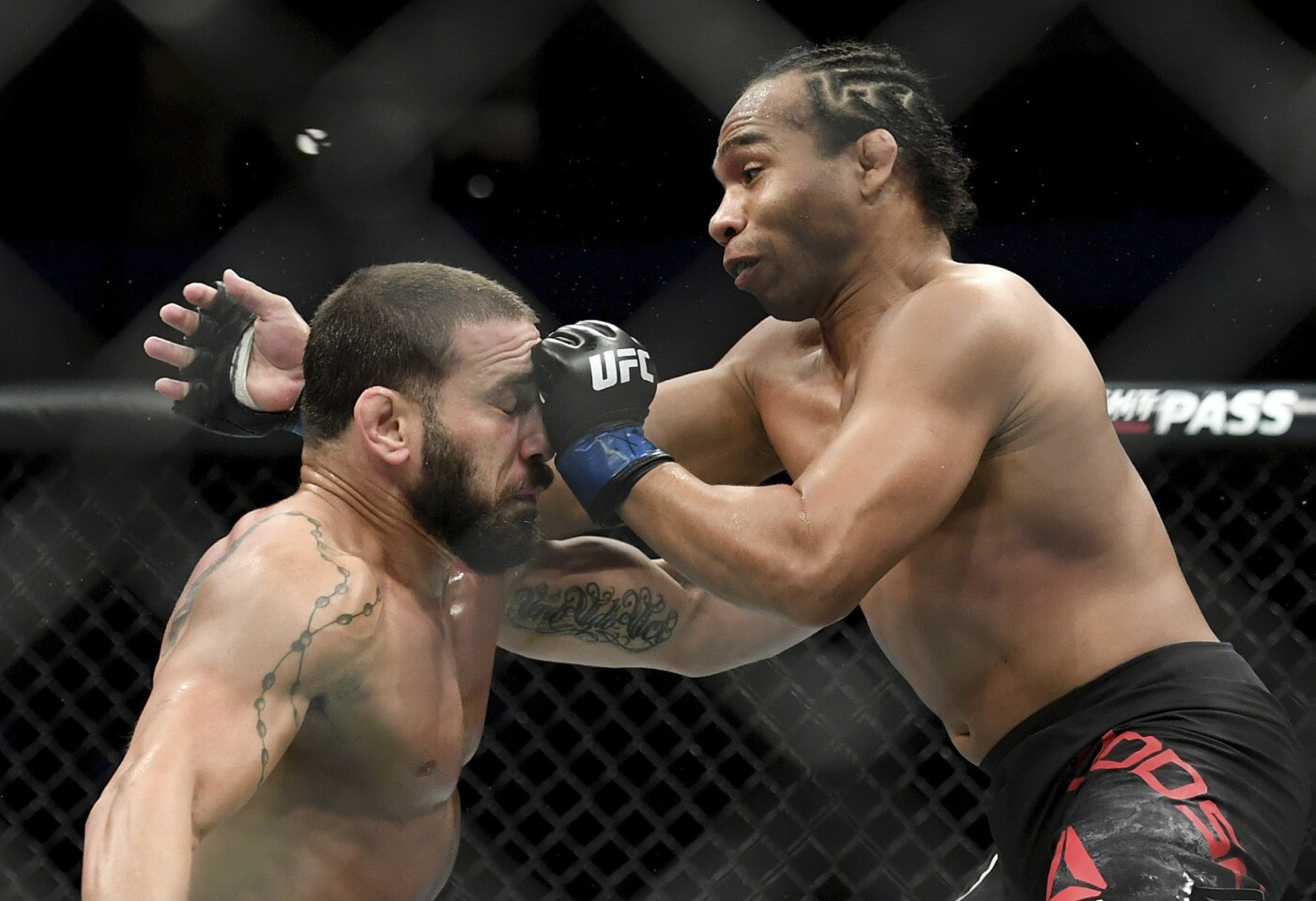 John Dodson, right, punches Jimmie Rivera during their bantamweight mixed martial arts bout at UFC 228 on Saturday, Sept. 8, 2018, in Dallas. (AP Photo/Jeffrey McWhorter)