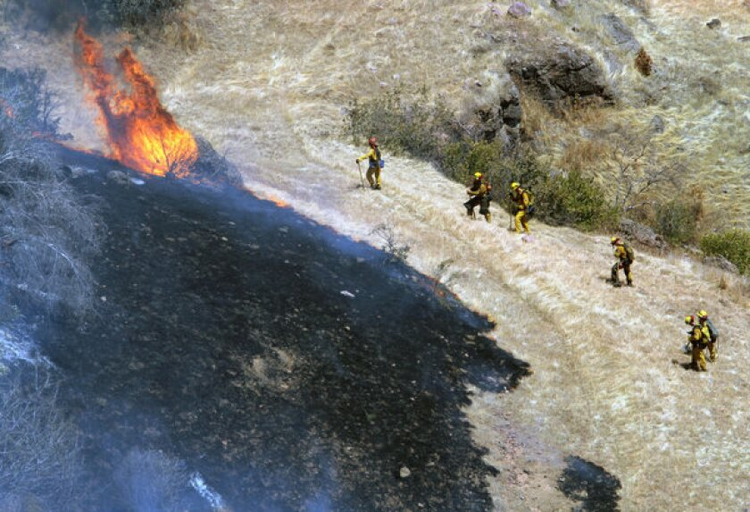 Butte County firefighters battle a vegetation fire in the canyon south of Neal Road after a plane crash-landed on the cliff side in Paradise, Calif.