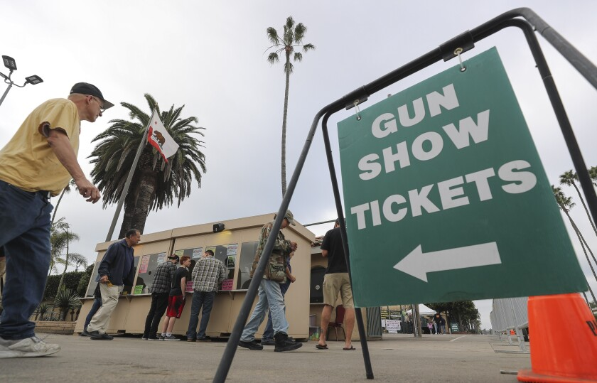 People buy tickets to the Crossroads of the West Gun Show at the Del Mar Fairgrounds on Saturday.