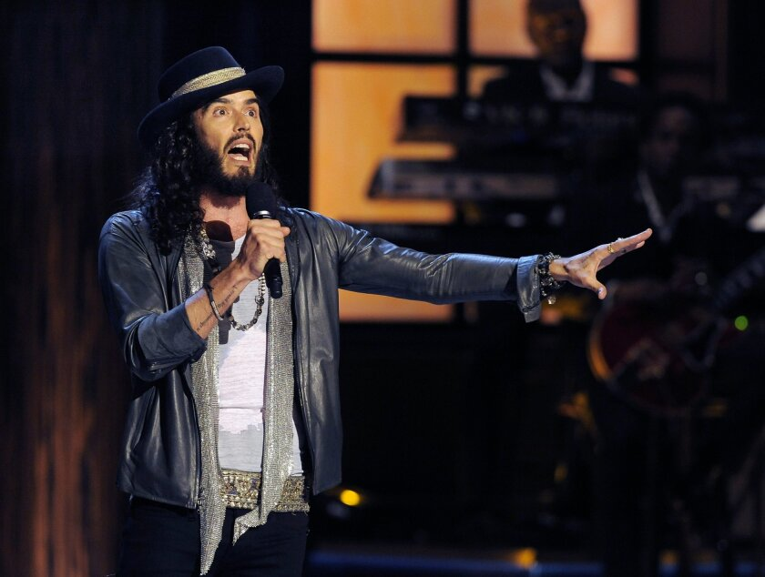 """FILE - In this Nov. 3, 2012 file photo, comedian Russell Brand performs at """"Eddie Murphy: One Night Only,"""" a celebration of Murphy's career, at the Saban Theater in Beverly Hills, Calif. Brand has a deal with Atria Books for a series called """"Russell Brand's Trickster Tales,"""" retellings of classic f"""