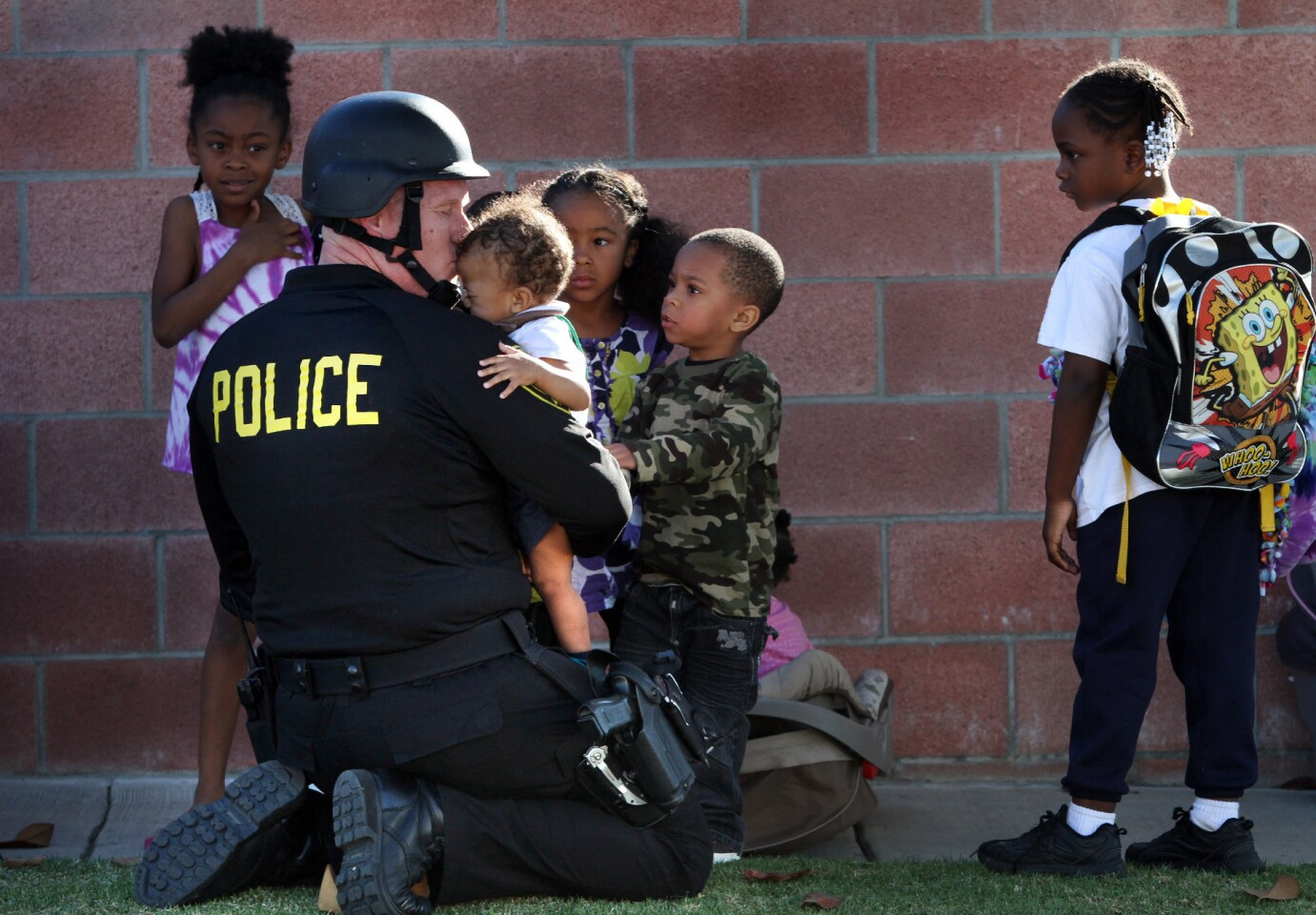 Inglewood police officer Joey Zeller kisses the head of a toddler he led to safety with a group of others from the neighborhood where two fellow officers were injured.