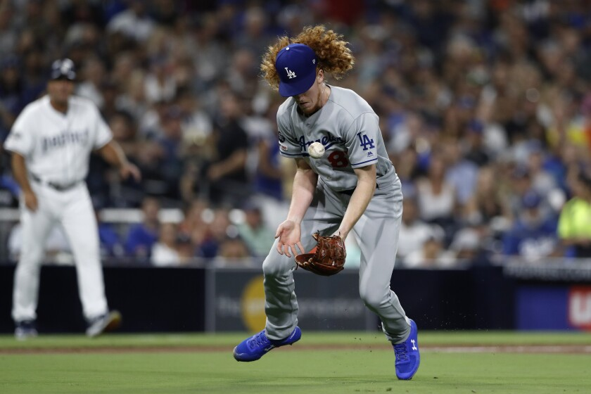 Dodgers pitcher Dustin May bobbles a ground ball before throwing out the Padres' Josh Naylor at first during the fourth inning of Monday's game.