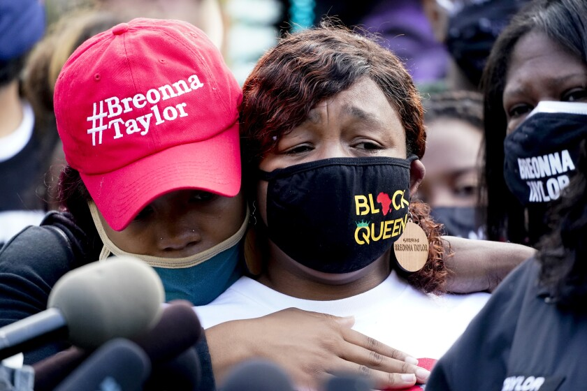 Tamika Palmer, right, the mother of Breonna Taylor, listens to a news conference Friday in downtown Louisville, Ky.