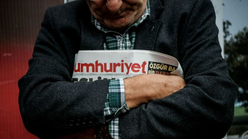 A man holds a copy of the latest edition of the Turkish daily newspaper Cumhuriyet during a demonstration outside its headquarters in Istanbul.