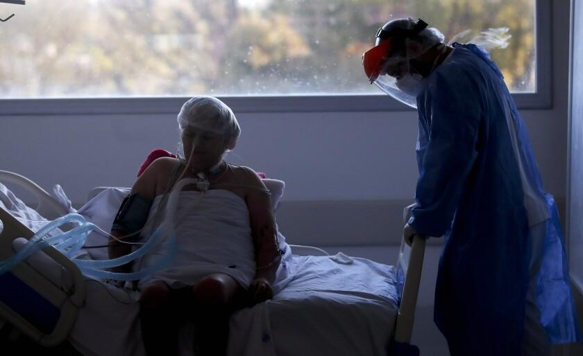 Un trabajador de la salud atiende a un paciente en una unidad de cuidados intensivos designada para personas infectadas con COVID-19 en un hospital en Buenos Aires, Argentina, el viernes 2 de octubre de 2020. (AP Foto/Natacha Pisarenko)
