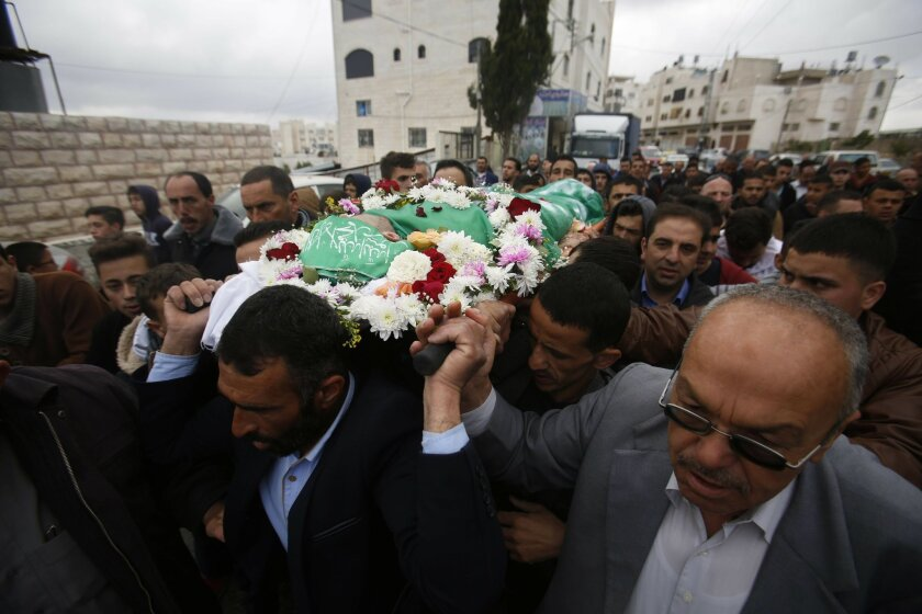 Palestinians chant slogans as they carry the body of Abdel-Fattah al-Sharif, during his funeral, in the West Bank city of Hebron, Saturday, May 28, 2016. Al-Sharif was killed by an Israeli soldier in March while lying on the ground seriously wounded after he and another Palestinian attacked IDF tro