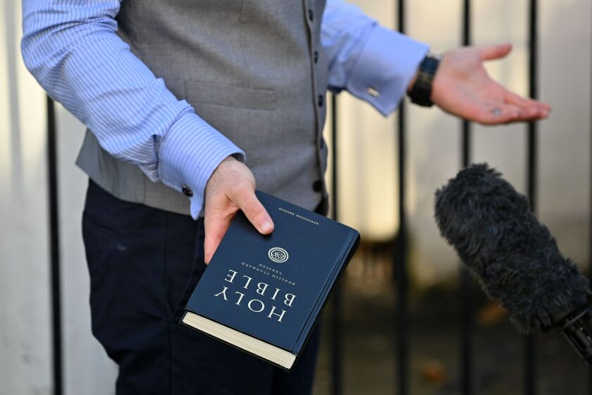 Pastor Regan King, of the Angel church in north London, holds a Bible.