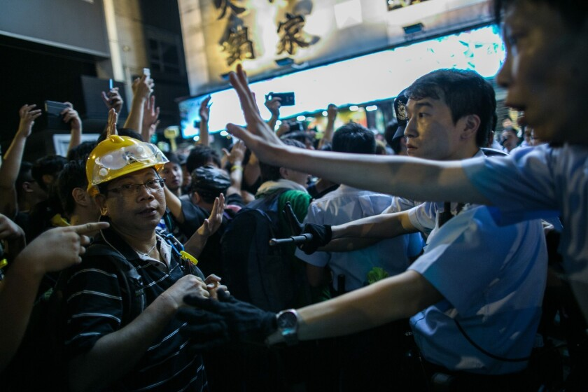 Demonstrators face off with police in the Mong Kok area of Hong Kong on Sunday as pro-democracy protests enter an eighth day.