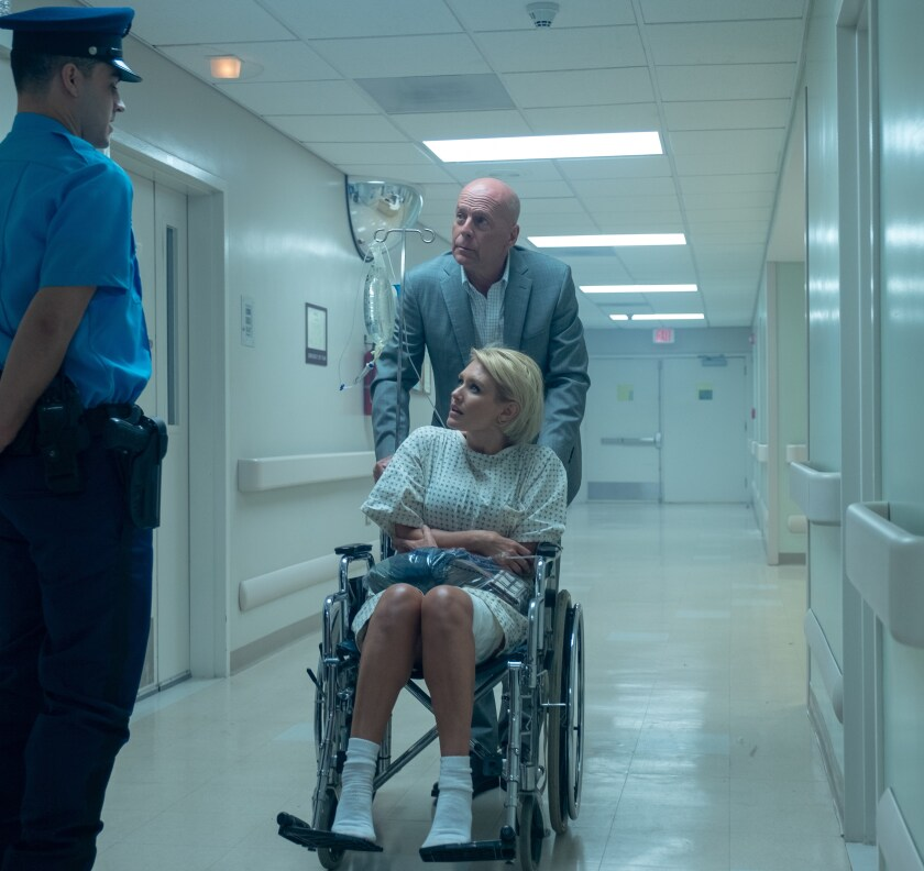 "Bruce Willis, back, and Nicky Whelan in a scene from ""Trauma Center."""