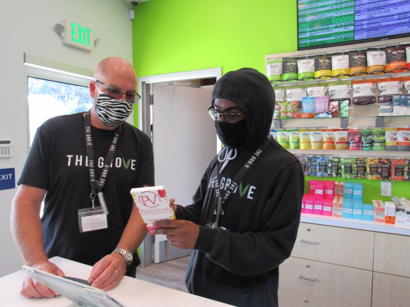 Sean McDermott (left), owner of The Grove cannabis shop in La Mesa, looks over one of the store's products with Larry Fennell, one of his first hires from the summer of 2018. The site on Center Street was the first in East County authorized by California to sell adult-use cannabis products. McDermott said he received confirmation from the state by mail on May 6 and The Grove had its first recreational cannabis product sale on May 7.