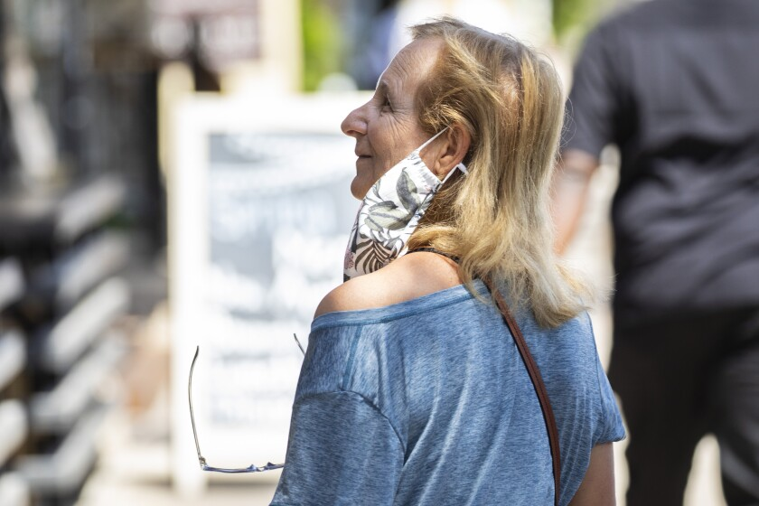 Redondo Beach, CA - May 14: A woman's mask hangs around one ear, not covering her face, while she walks along S. Catalina Avenue in the Riviera Village shopping area of Redondo Beach, CA, a day after the Centers for Disease Control and Prevention (CDC) loosened guidelines for vaccinated people, with masks no longer being necessary when outdoors or in most indoor situations, Friday, May 14, 2021. The new guidelines state that fully vaccinated people no longer need to wear a mask or physically distance in any setting, except where required by federal, state, local, tribal, or territorial laws, rules, and regulations, including local business and workplace guidance. (Jay L. Clendenin / Los Angeles Times)