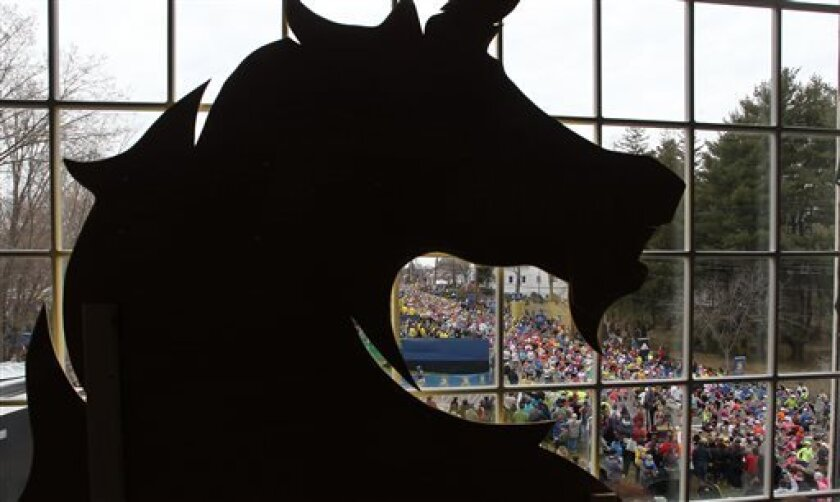 Behind a silhouette of the Boston Athletic Association logo, runners start the 117th running of the Boston Marathon, in Hopkinton, Mass., Monday, April 15, 2013. (AP Photo/Stew Milne)