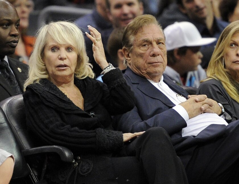 FILE - In this Nov. 12, 2010 file photo, Los Angeles Clippers owner Donald T. Sterling, right, sits with his wife Shelly during the Clippers NBA basketball game against the Detroit Pistons in Los Angeles. Donald Sterling has agreed to surrender his stake of the Clippers to his wife, and she is movi