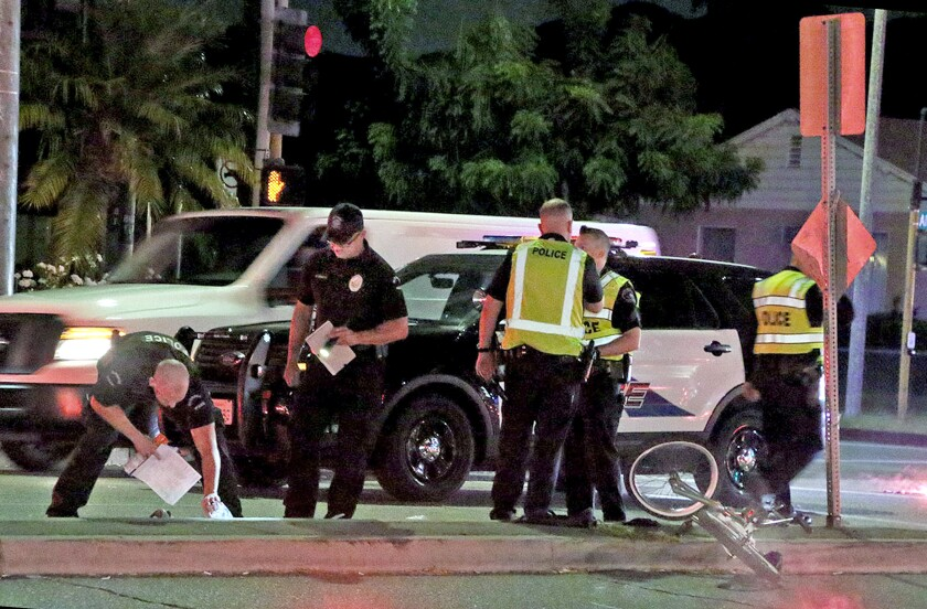 Burbank police traffic investigators analyze the scene of a vehicle collision near the intersection of Alameda Avenue and Lake Street on Thursday after a 16-year-old bicyclist was struck by a vehicle and suffered serious injuries.