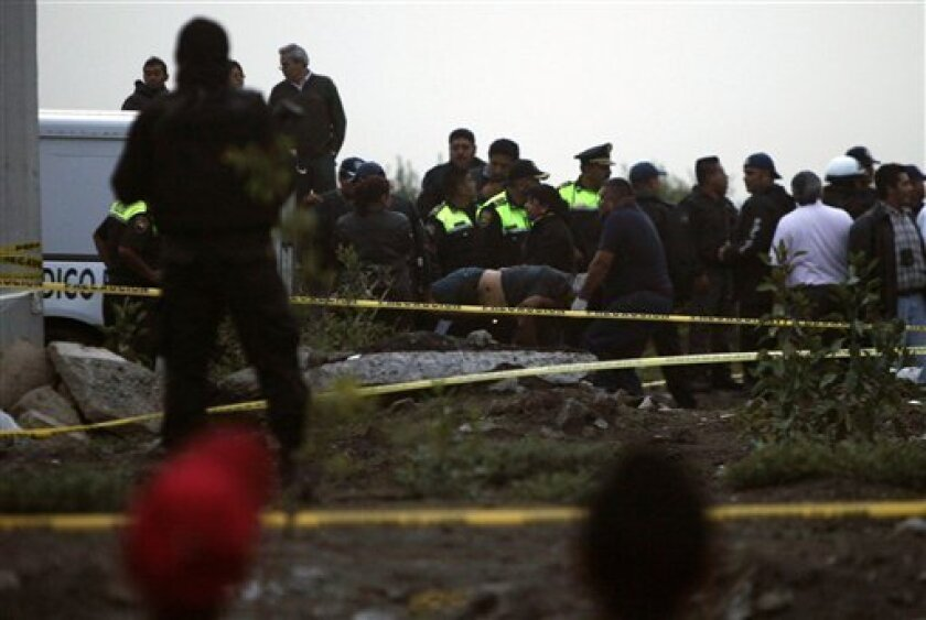 Police and forensic workers carry bodies in Valle de Chalco, Mexico, Friday, July 8, 2011. Mexican police have found the bodies of 10 men and a woman scattered near a water well on the outskirts of Mexico City. (AP Photo/Moises Castillo)