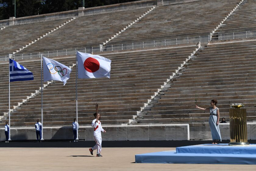 At a scaled-down ceremony at Panathenaic Stadium in Athens on Thursday, only a few people were permitted to watch Greek officials hand the traditional flame to the Tokyo 2020 organizing committee.