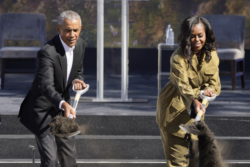 Former President Barack Obama, left, and former first lady Michelle Obama toss shovels of dirt during a groundbreaking ceremony for the Obama Presidential Center Tuesday, Sept. 28, 2021, in Chicago. (AP Photo/Charles Rex Arbogast)