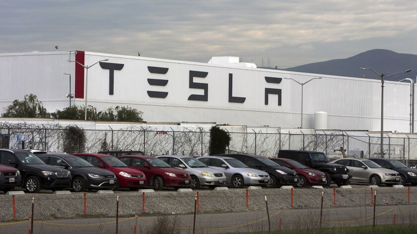 Cars are lined up near the Tesla Motors factory complex in Fremont, Calif., on Thursday, Jan. 28, 2016.
