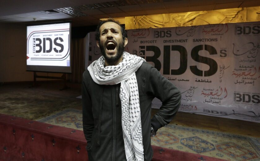 FILE - In this April 20, 2015, file photo, an Egyptian man shouts anti-Israeli slogans in front of banners with the Boycott, Divestment and Sanctions (BDS) logo during the launch of the Egyptian campaign that urges boycott, divestment and sanctions against Israel and Israeli-made goods, at the Egyp