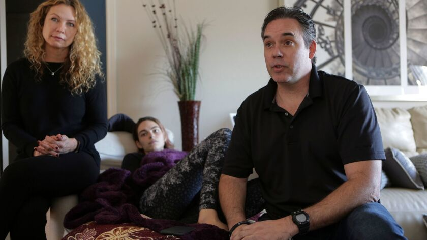 Kira Stanley, 15, at her Encinitas home Friday with her mother, Wendy Stanley, and father, Robert St