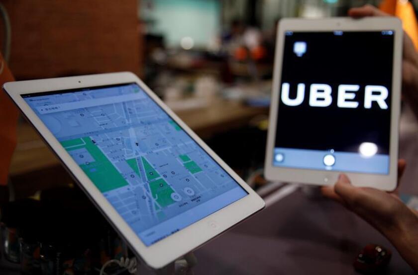 Un logotipo y una aplicación de Uber se muestran en dispositivos móviles durante una conferencia de prensa. EFE/Archivo