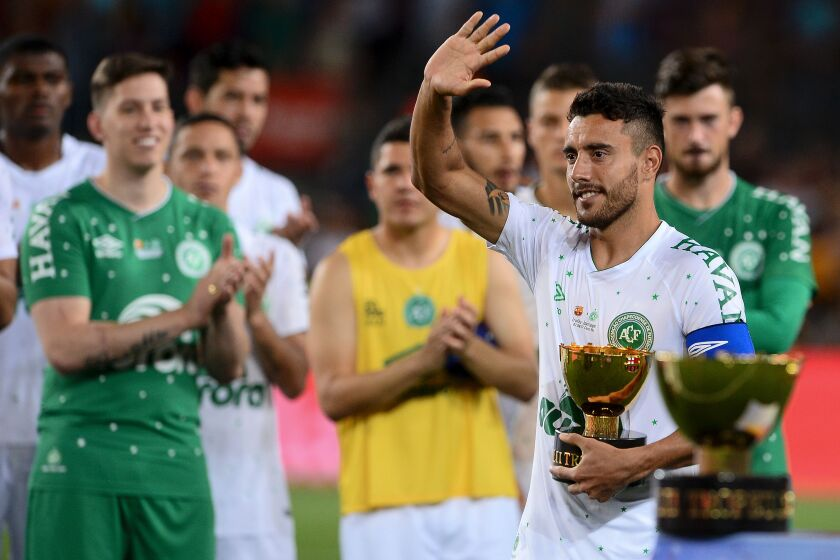 Chapecoense's defender Alan Ruschel waves to Barcelona players as he holds the second place trophy after the 52nd Joan Gamper Trophy friendly football match between Barcelona FC and Chapecoense at the Camp Nou stadium in Barcelona on August 7, 2017. / AFP PHOTO / Josep LAGOJOSEP LAGO/AFP/Getty Images