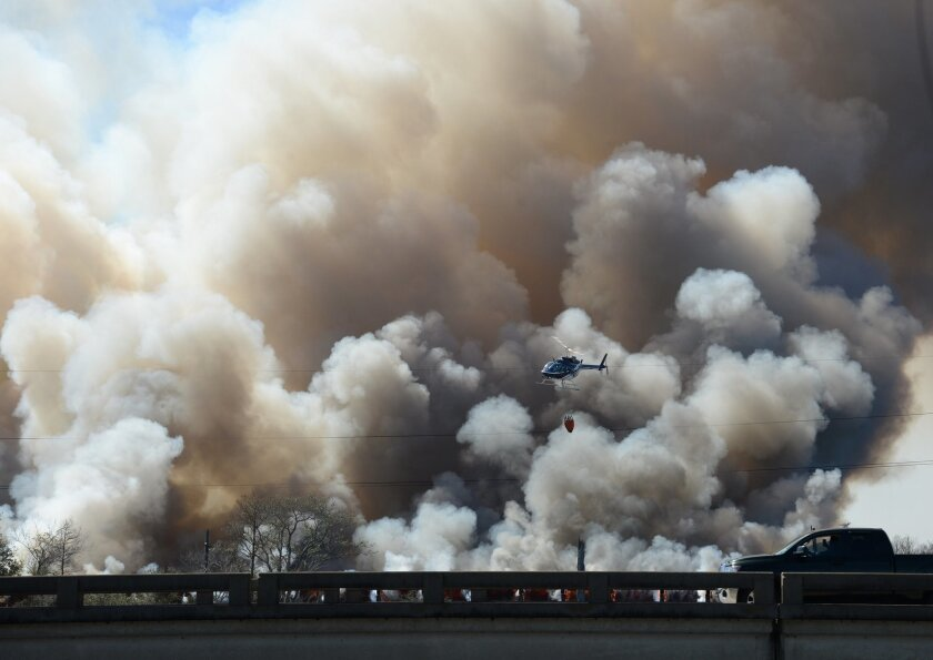 A helicopter flies past plumes of smoke during firefighting efforts on a train trestle parallel to Interstate 10 near the Bonnet Carre Spillway, west of New Orleans on Saturday, Feb. 13, 2016. A CN Railway spokesman says it typically carries four to eight freight trains a day, plus one passenger tr