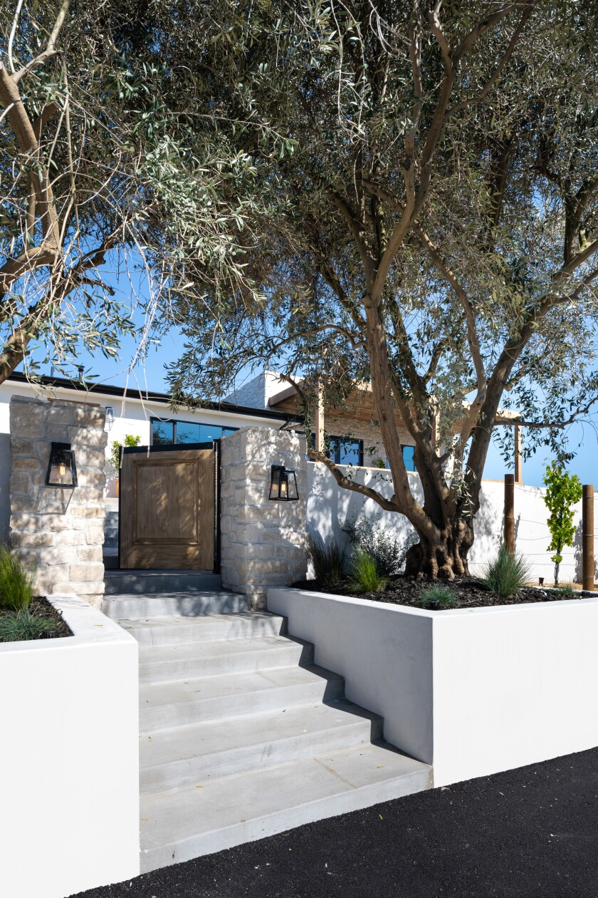 The olive trees flanking the front gate help define the entrance to the home.