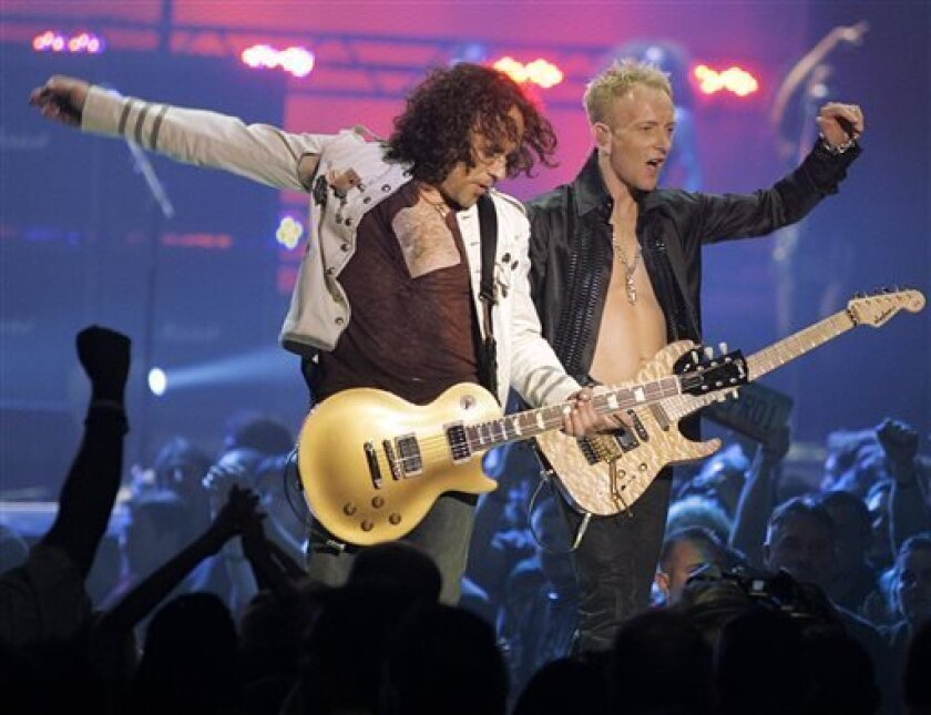 Vivian Campbell, left, and Phil Collen, right, of rock group Def Leppard perform in Las Vegas. In a statement Monday, June 10, 2013, Campbell disclosed he has Hodgkin's Lymphoma and had been in chemotherapy for two months, with four months to go. He is still in the band. (AP Photo/Jae C. Hong, file)