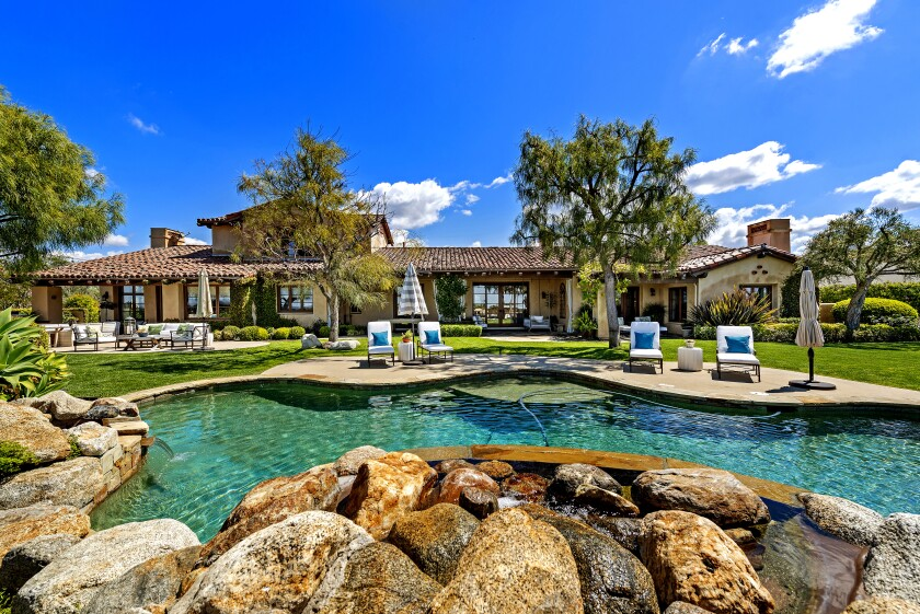 The one-acre property sits behind gates and has a putting green, a resort-style swimming pool, lawn and golf course views.