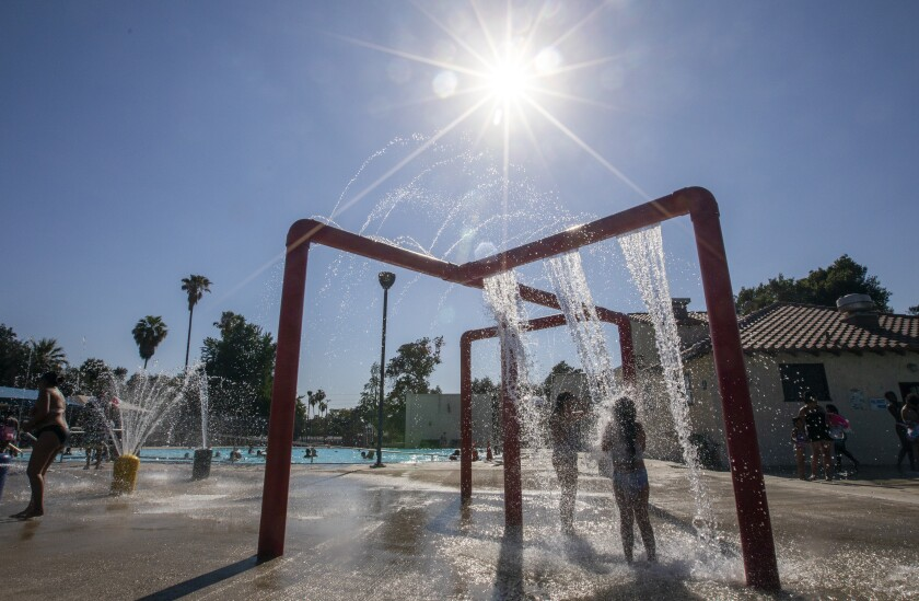 Children play in the water of a park fountain beneath a bright sun.