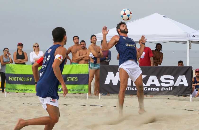 """Phillippe """"Shrek"""" Happ uses his head to knock the ball over the net during a footvolley tournament in Carlsbad. At left is teammate Bruninho Barros."""