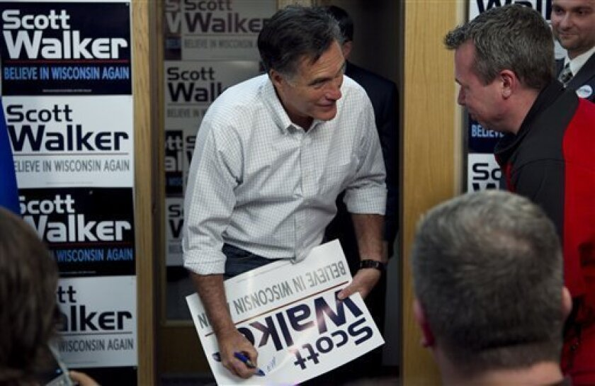 Republican presidential candidate, former Massachusetts Gov. Mitt Romney signs placards for supporters of Wisconsin Republican Gov. Scott Walker at a phone bank during a campaign stop in Fitchburg, Wis., Saturday, March 31, 2012.  The phone bank is used in support of Walker who is facing a recall e