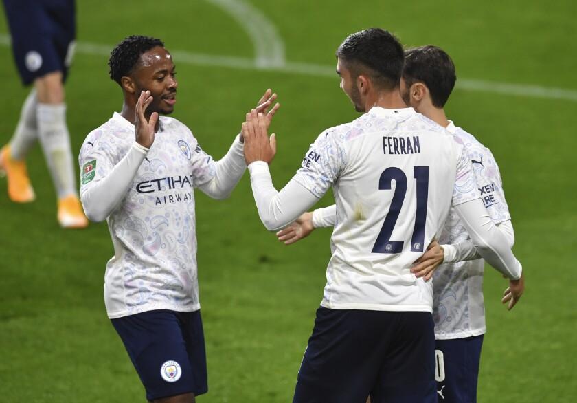Ferrán Torres (derecha), del Manchester City, es felicitado tras anotar el tercer tanto ante el Burnley, en un encuentro de la Copa de la Liga inglesa, disputado el miércoles 30 de septiembre de 2020 (Paul Ellis/Pool via AP)