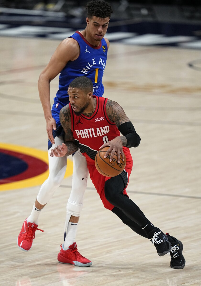 Portland Trail Blazers guard Damian Lillard (0) drives to the basket against Denver Nuggets forward Michael Porter Jr. (1) during the second half of Game 5 of a first-round NBA basketball playoff series Tuesday, June 1, 2021, in Denver. (AP Photo/Jack Dempsey)