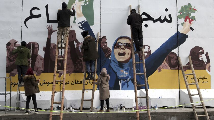 Independent Afghan artists draw a graffiti on a barrier wall of the Ministry of Women's Affairs to m