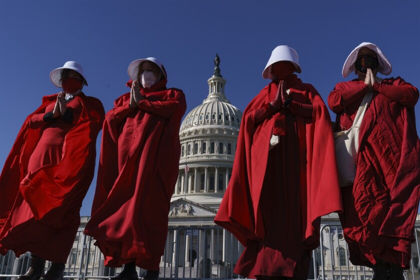 Activists dressed in red robes and white hats in Washington, D.C.