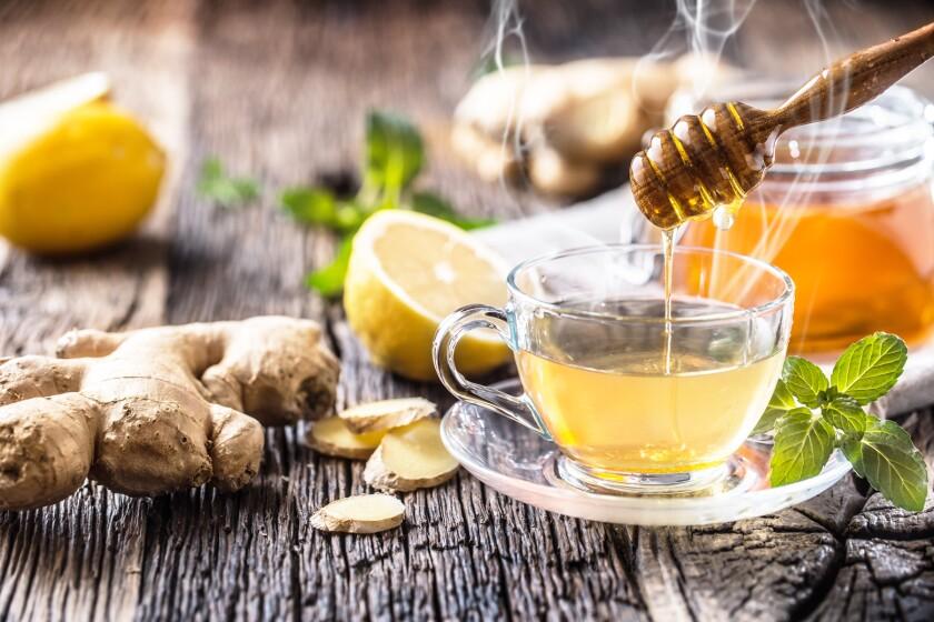 Ginger tea with honey, lemon and mint leaves.