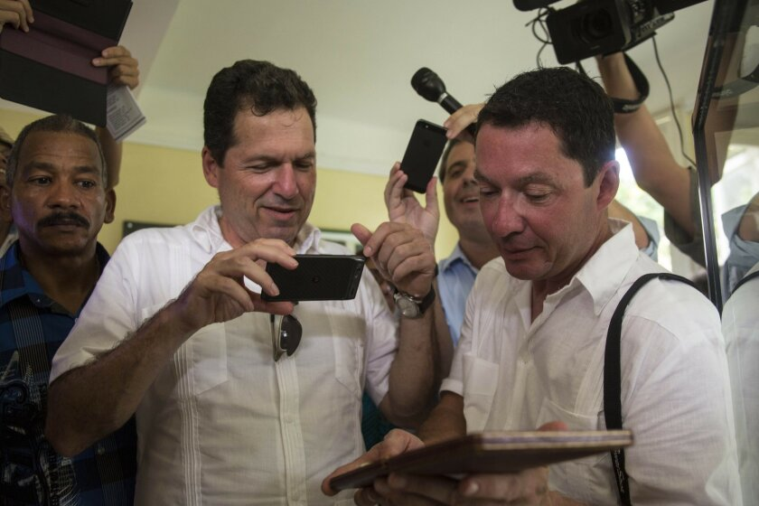John Hemingway, left, takes photos of the Nobel Prize medal received 60 years ago his grandfather Ernest Hemingway, while his brother Patrick holds the medal during a visit to the home of late American author in Finca Vigia, Cuba, Thursday, Sept. 11, 2014. Cuba's National Cultural Heritage Council said Thursday that marine scientists on a tour with the author's grandsons wouldn't be able to see the authors fishing logs but will work to let researchers see them eventually. (AP Photo/Ramon Espinosa)