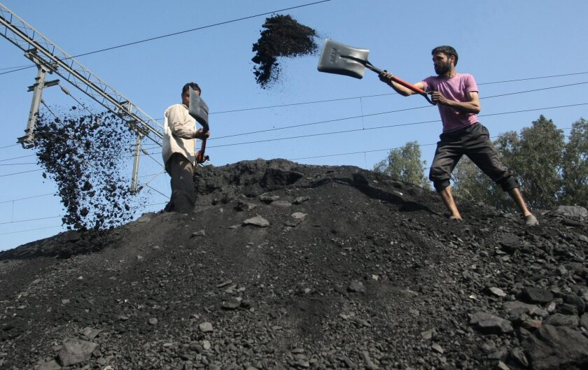 Indian laborers load coal into trucks near the city of Jammu on Feb. 4.