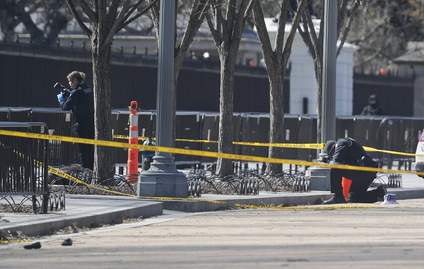 Law enforcement officers photograph the area where a man shot himself to death in front of the White House on March 3, 2018.