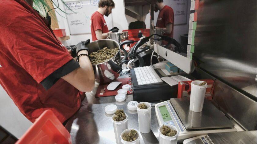 In this Friday, Jan. 12, 2018 photo a bud tender prepares marijuana for a customer at Med Men a disp