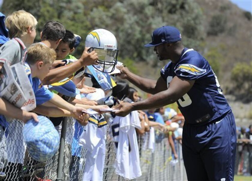 San Diego Chargers linebacker Dwight Freeney signs autographs for fans during NFL football training camp Thursday, Aug. 1, 2013, in San Diego. (AP Photo/Denis Poroy)