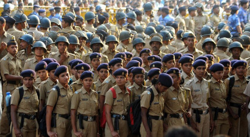 Indian policemen and women stand guard outside Shiv Sena chief Bal Thackeray's residence following his death today after being critically ill from last few days. Thousands of anxious supporters gathered outside Thackeray's house, and more than 1500 policemen were deployed in the area to maintain the peace.