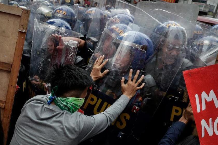 Policía antidisturbios y activistas se enfrentan durante una protesta contra Trump, cerca de la embajada de los EE.UU. en Manila (Filipinas). EFE