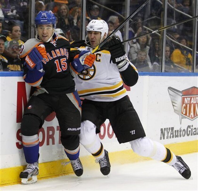 New York Islanders PA Parenteau (15) is checked by Boston Bruins' Zdeno Chara (33) during the second period of an NHL hockey game at the Nassau Coliseum in Uniondale, N.Y., Saturday, March 31, 2012. (AP Photo/Paul J. Bereswill)